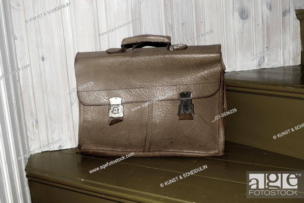 Stock Photo: An old leather briefcase is standing on a staircase. An old leather briefcase is standing on a staircase.