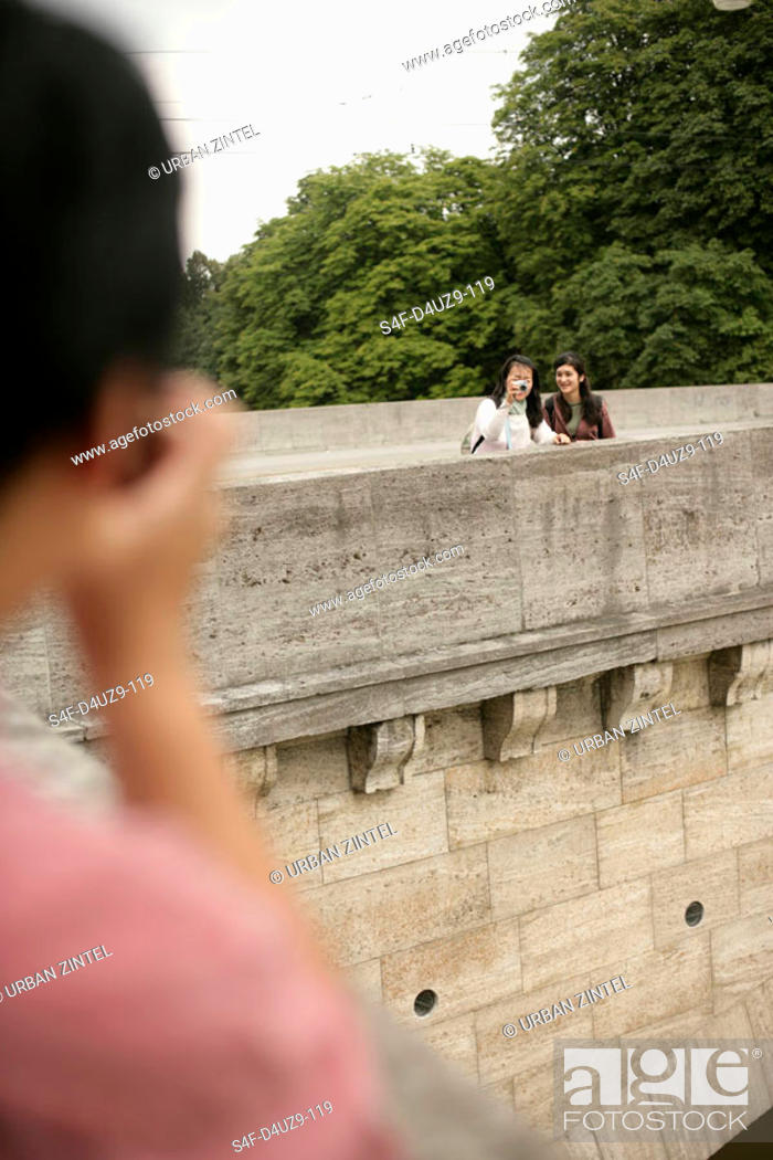 Stock Photo: Man taking a picture of two Asian women on a stone-bridge, selective focus.