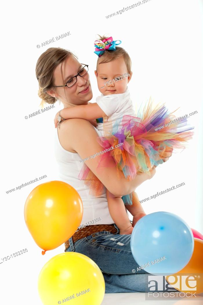 Stock Photo: Very young mother with baby girl celebrating first birthday.