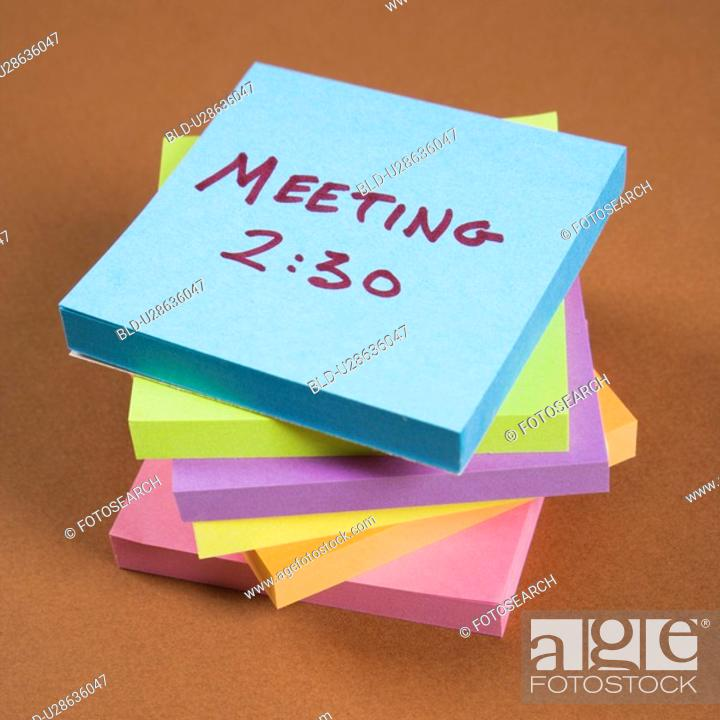 Stock Photo: Stack of sticky notes with a meeting reminder.