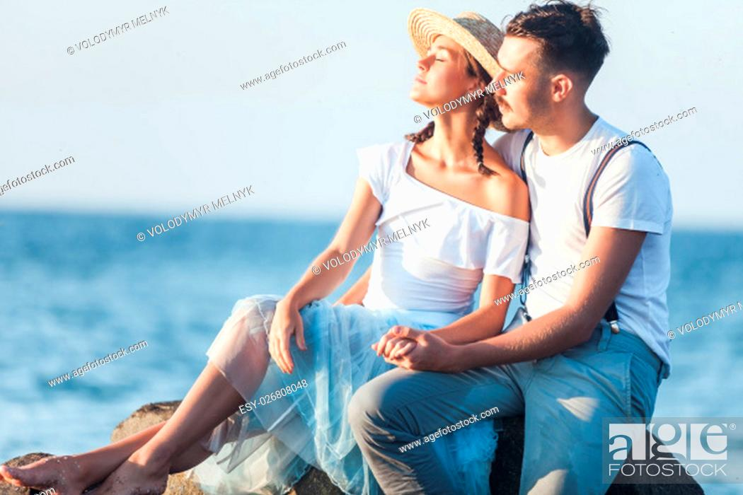 Stock Photo: Happy young romantic couple relaxing on the beach watching the sunset.