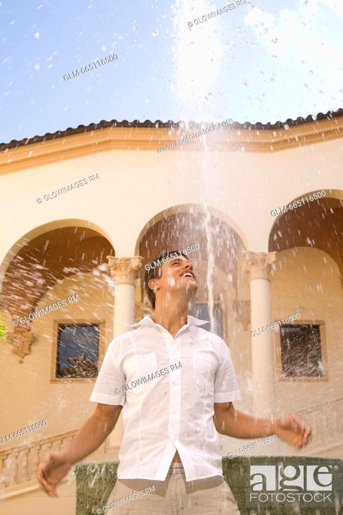 Stock Photo: Man playing with water under a fountain, Biltmore Hotel, Coral Gables, Florida, USA.