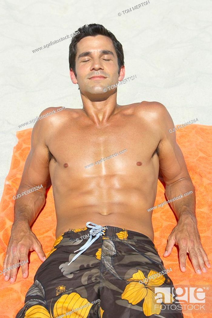 Stock Photo: Man lying down on beach towel in sand.