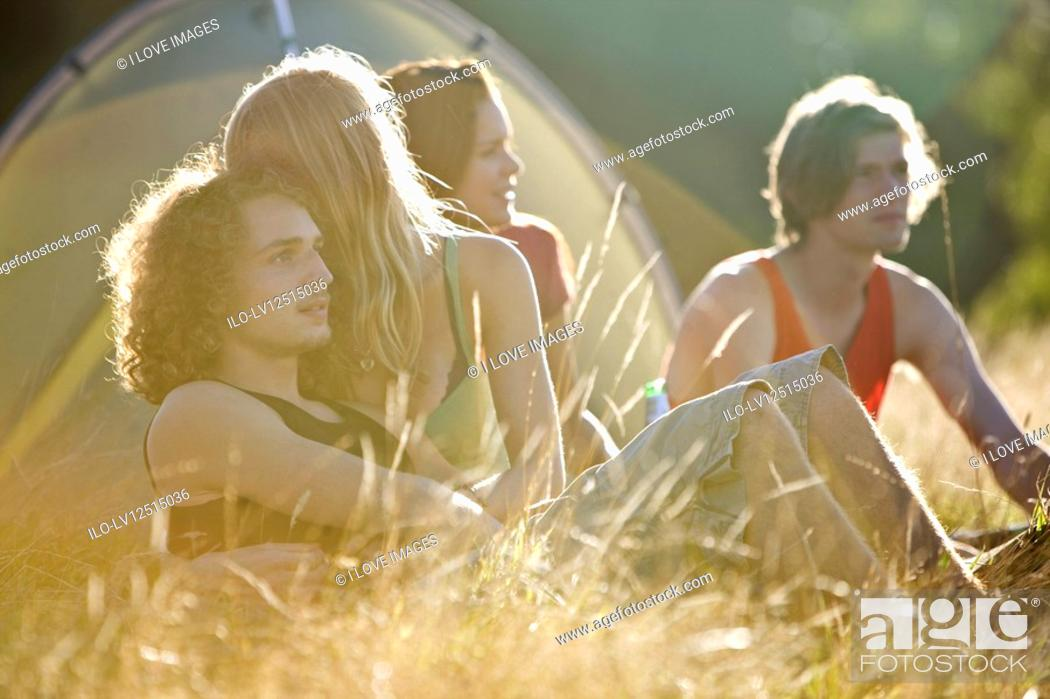 Stock Photo: Two young couples sitting in front of a tent.