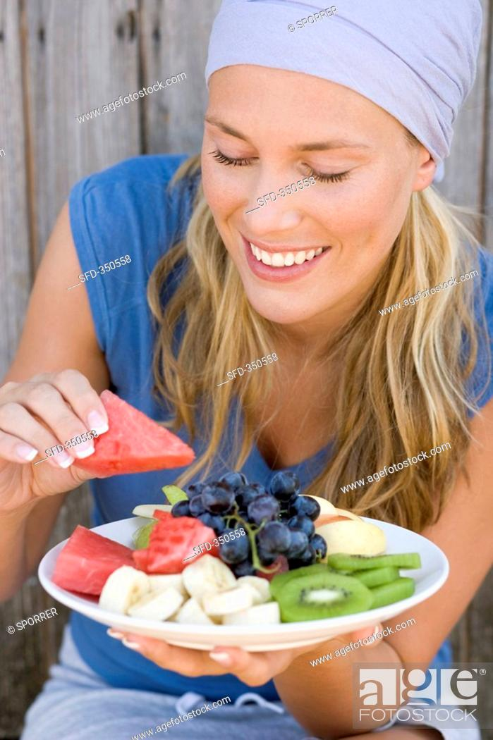 Stock Photo: Woman eating watermelon from a plate of fruit.