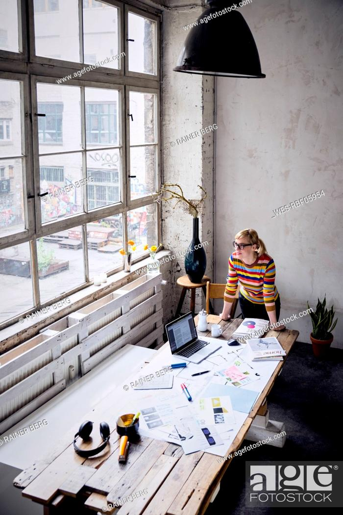 Stock Photo: Woman standing at desk in a loft looking through window.