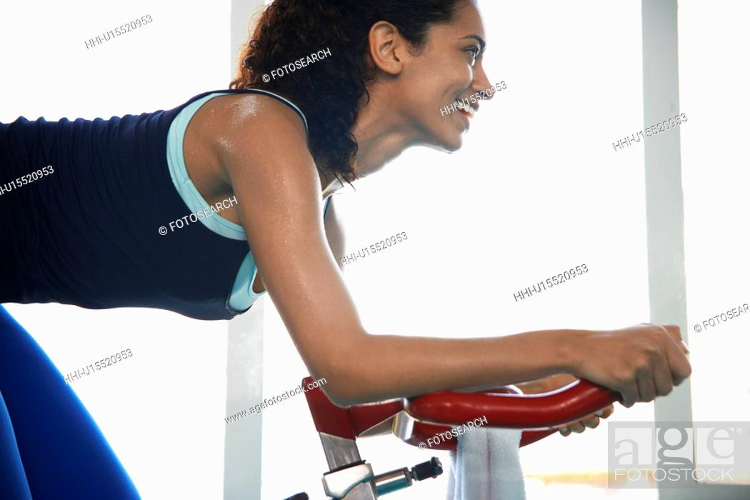 Stock Photo: Young woman indoor cycling.