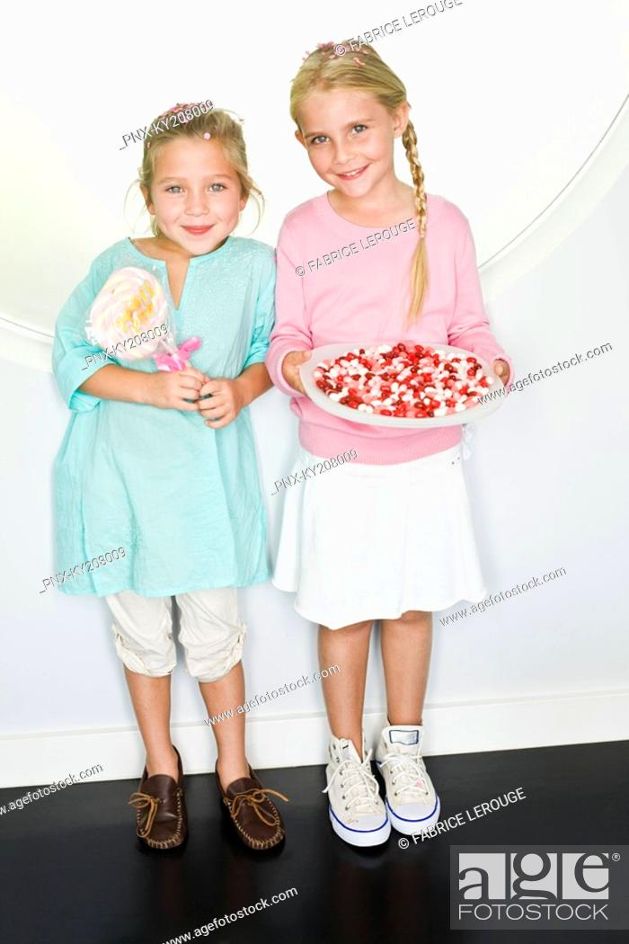 Stock Photo: Girl holding a plate of jelly beans with her friend standing beside her.