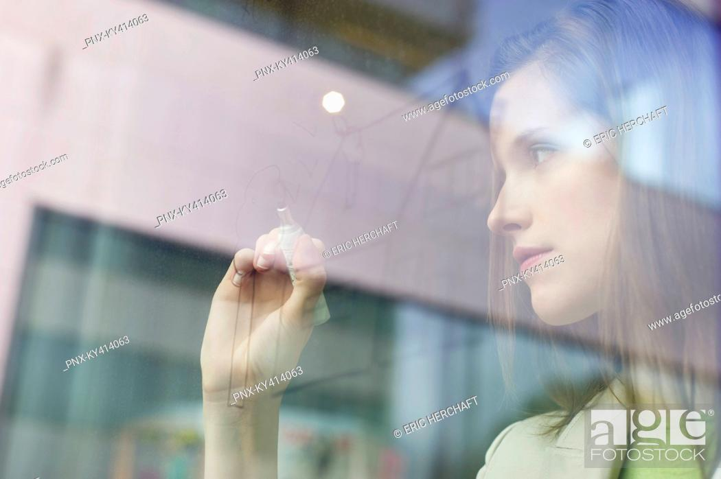 Stock Photo: Businesswoman drawing a house on a glass surface.