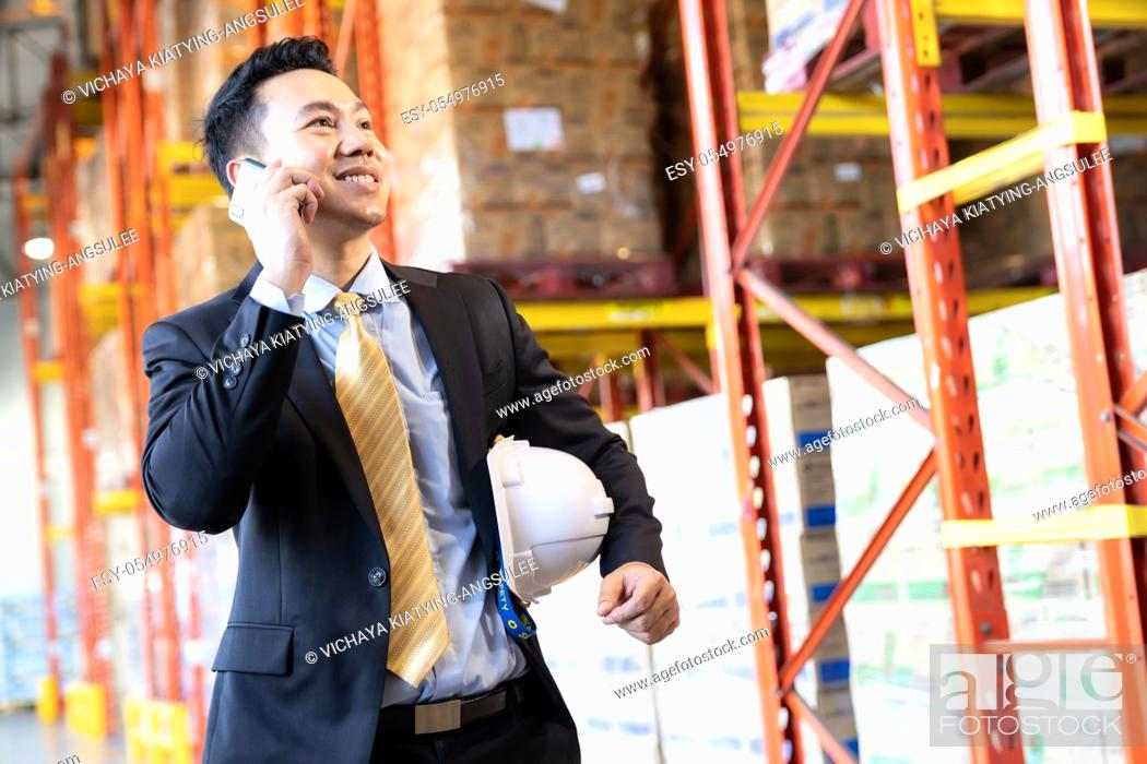 Stock Photo: Portrait of asian confidence businessman investor stand and making a call with mobile phone in large factory and distribution warehouse environment.
