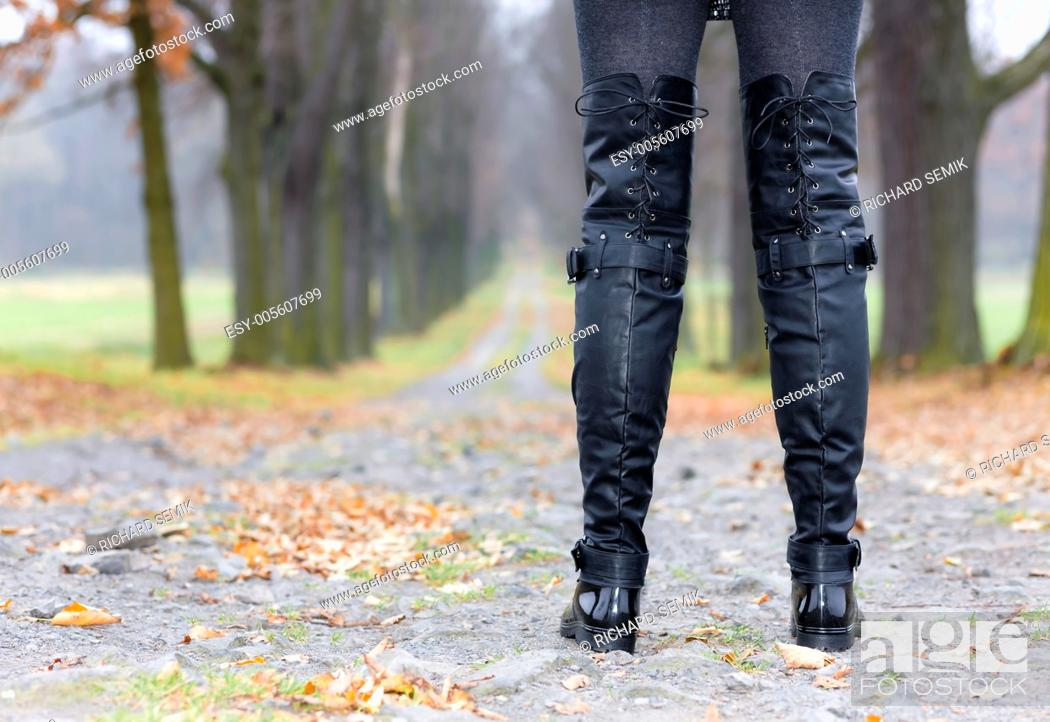 Stock Photo: detail of woman wearing black clothes and boots in autumnal alley.