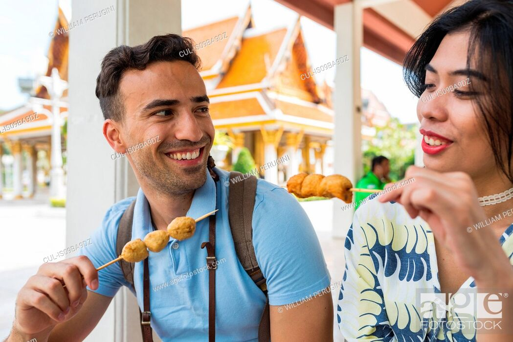Stock Photo: Young tourist couple eating skewered street food outside temple, Bangkok, Thailand.
