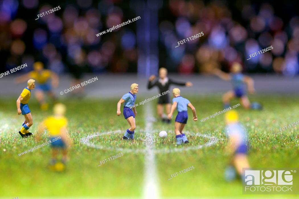 Stock Photo: Miniature soccer player figurines at the kick-off of a soccer match.