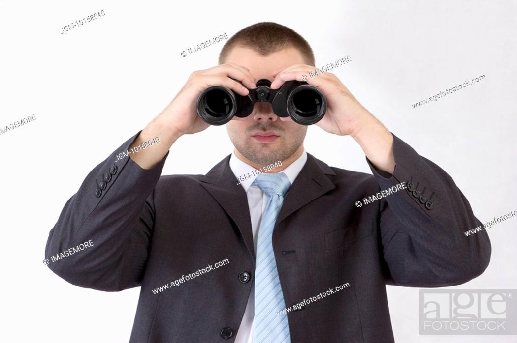 Stock Photo: Businessman holding a binocular telescope.