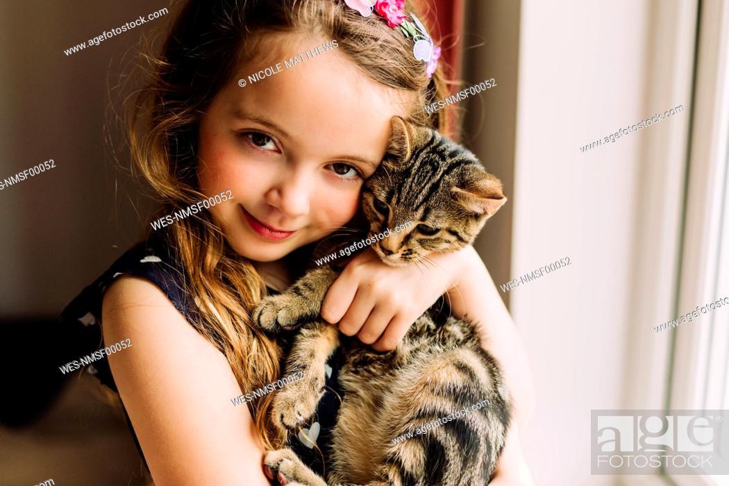 Stock Photo: Portrait of little girl holding tabby kitten.