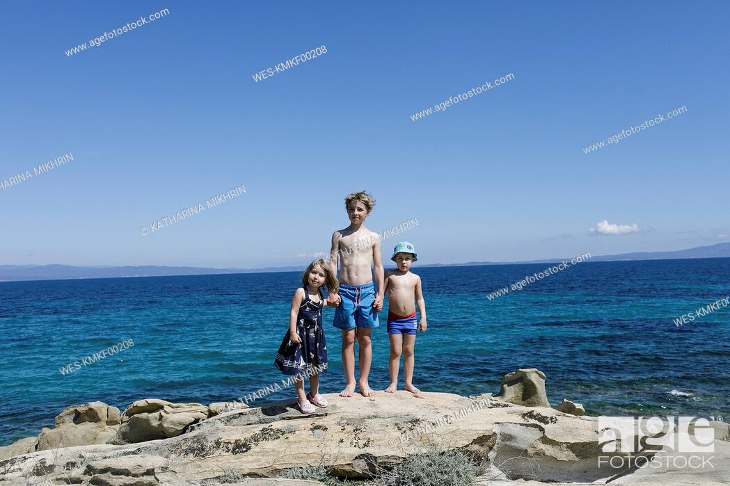 Stock Photo: Greece, Chalkidiki, three children stamnding hand in hand on rock in front of the sea.