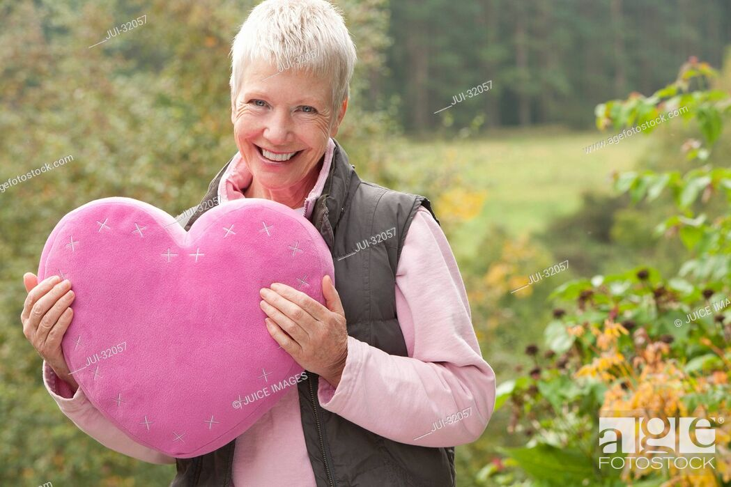 Stock Photo: Portrait of smiling woman holding heart-shape pillow in garden.