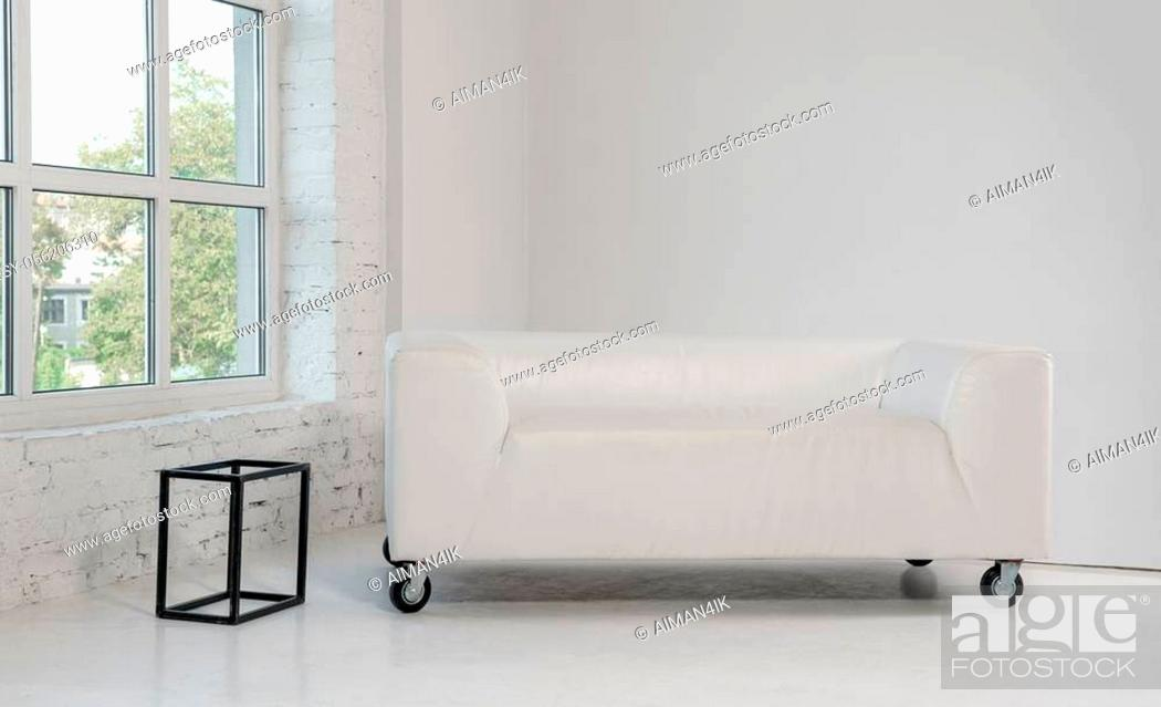 Stock Photo: Modern leather white couch and wire frame side table in white room.