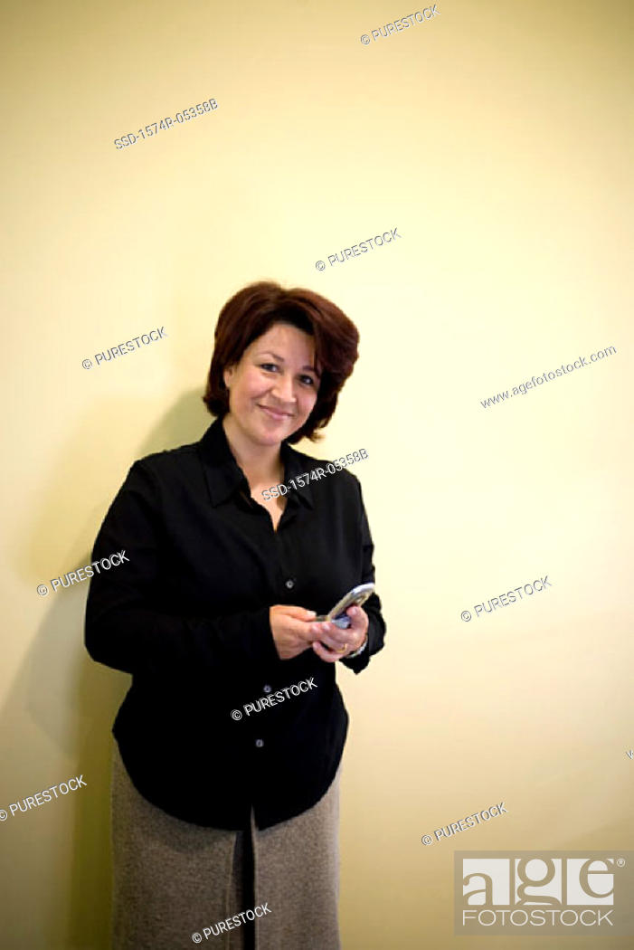 Stock Photo: Portrait of a businesswoman standing in an office holding a mobile phone.