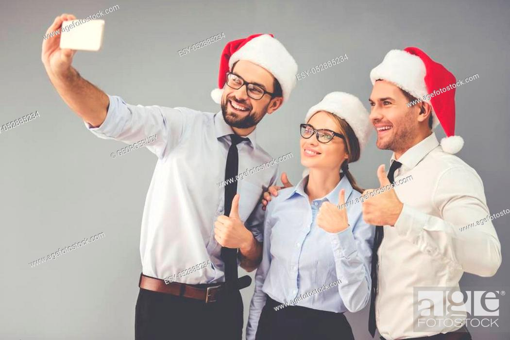 Stock Photo: Happy business people in Santa hats are doing selfie and smiling while celebrating New Year, on gray background.