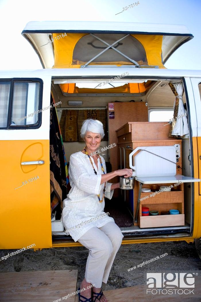 Stock Photo: Senior woman making tea in camper van, smiling, portrait.