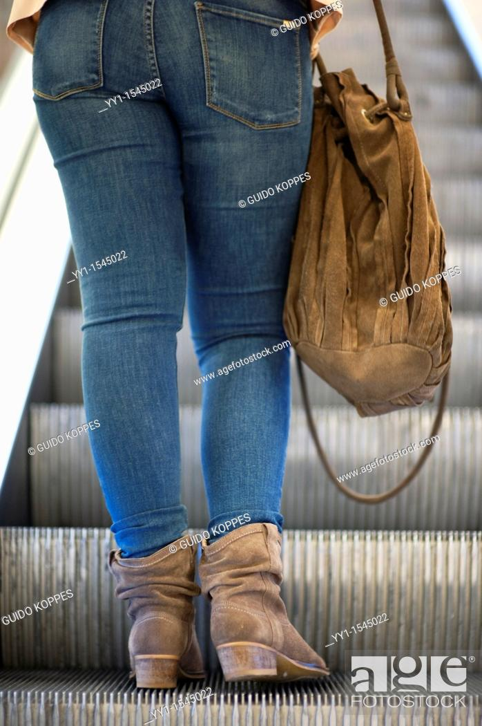 """Stock Photo: Rotterdam, Netherlands. Female shopper and customer of upscale and luxurious department store: """"""""De Bijenkorf"""""""", taking the escalator toward another department."""