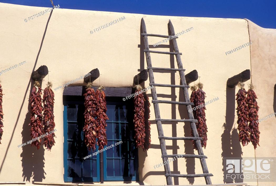 Stock Photo: chili peppers, Taos, NM, New Mexico, Clusters of chili peppers hanging to dry outside an adobe style building in the village of Taos.