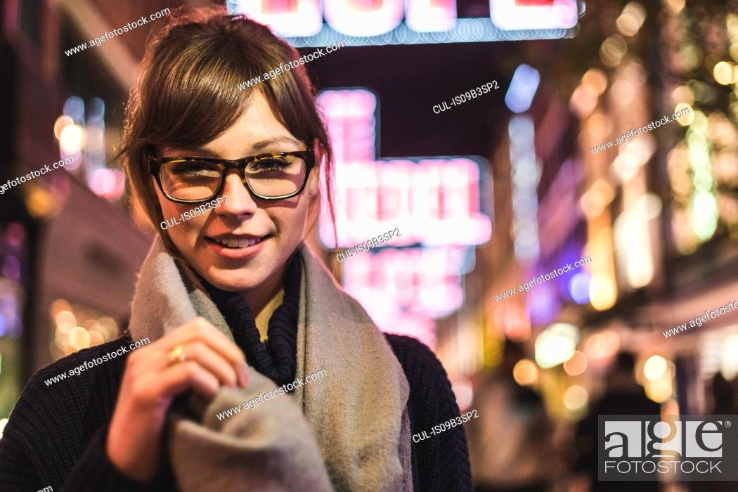 Stock Photo: Portrait of young woman in illuminated street at night.
