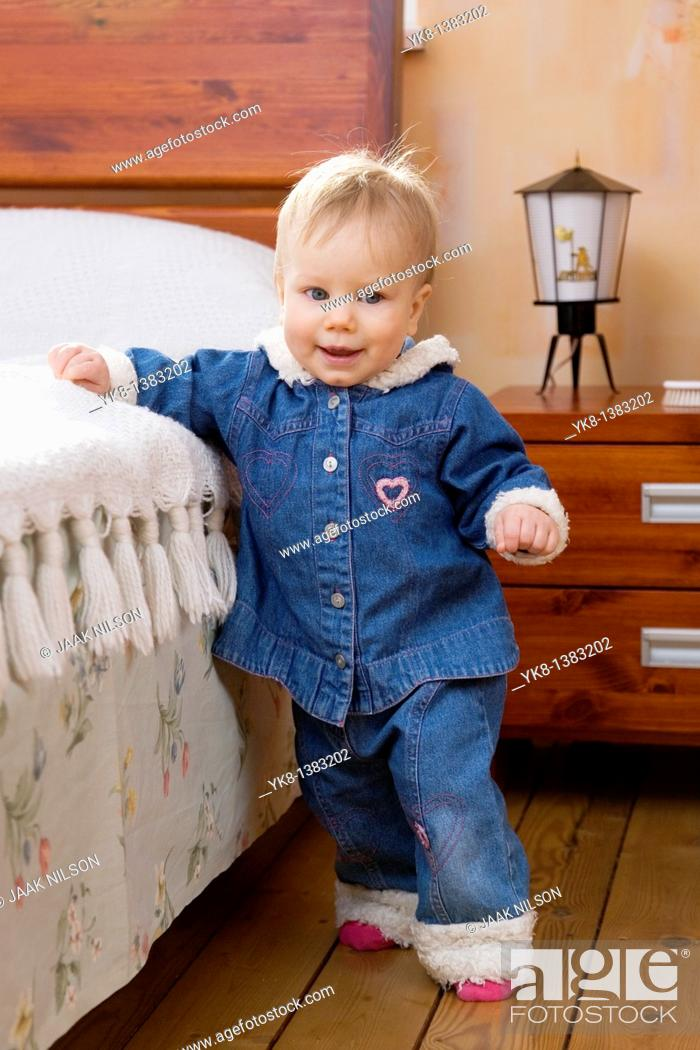 Stock Photo: Happy Smiling Ten Month Old Baby Walking First Steps by Bed.
