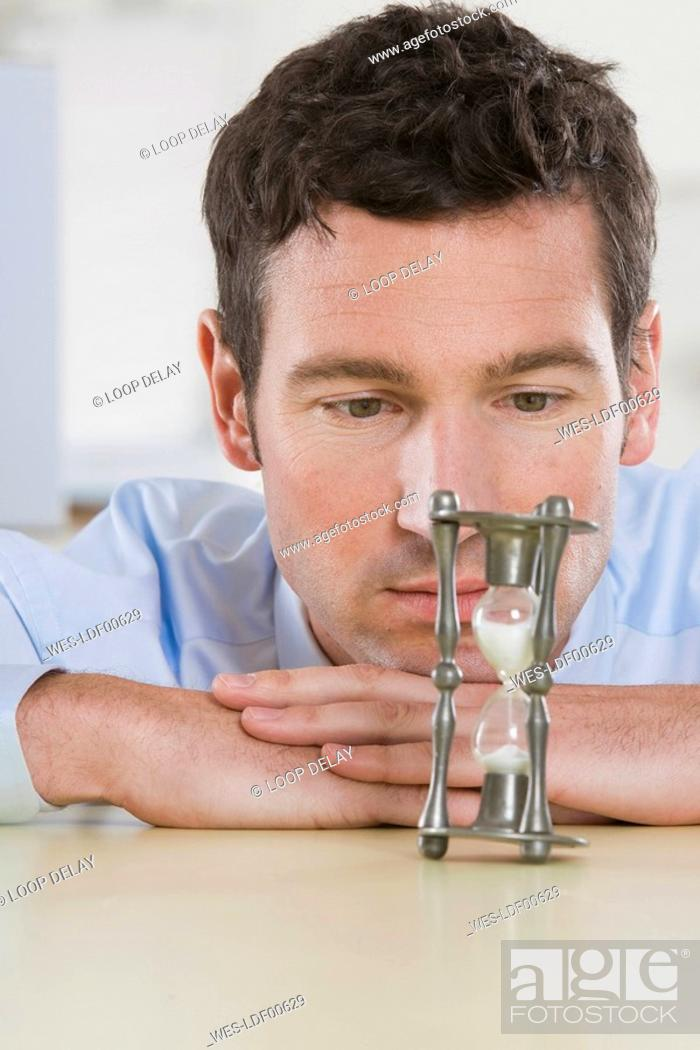Stock Photo: Germany, Munich, young businessman looking at hour glass on office desk, portrait.