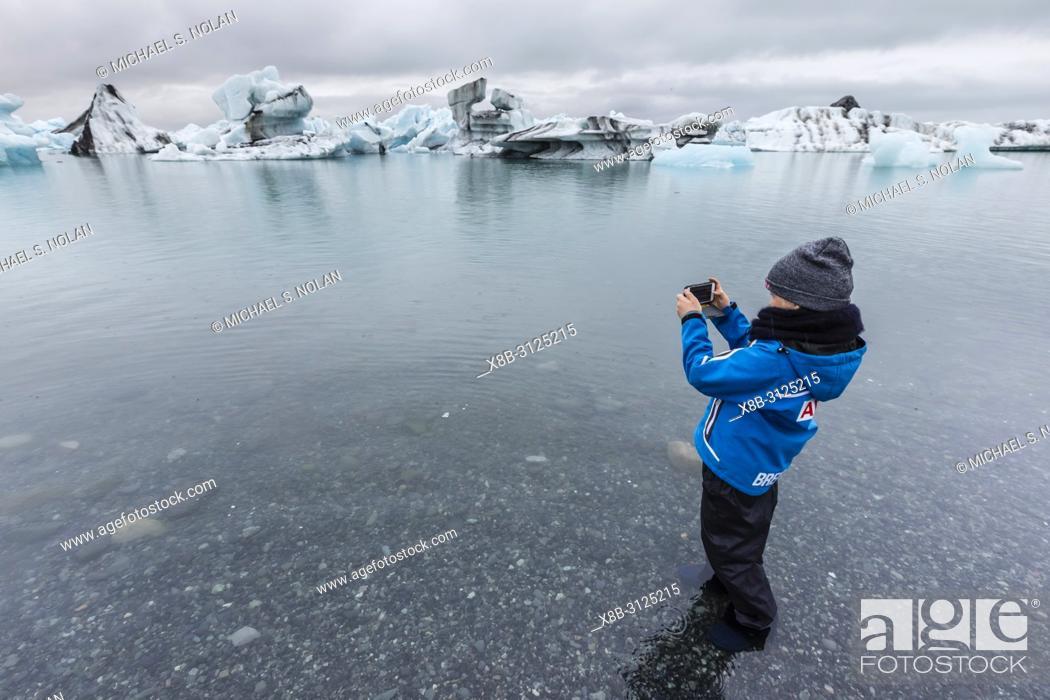 Stock Photo: Girl photographing calved ice from the Breidamerkurjokull glacier in Jökulsárlón glacial lagoon, Iceland.