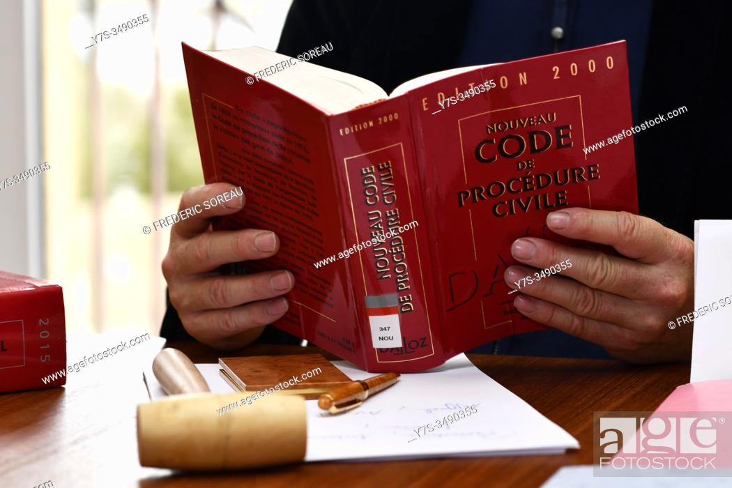 Stock Photo: Man reading code of civil procedure, France.