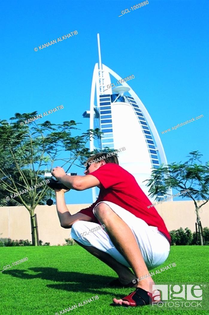 Stock Photo: Western tourist taking pictures in front of Burj Al Arab hotel in Dubai, UAE.