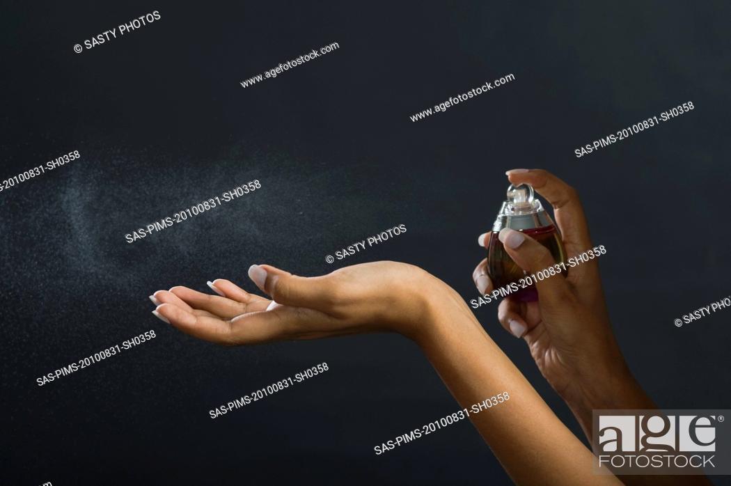 Stock Photo: Woman applying perfume on her hand.