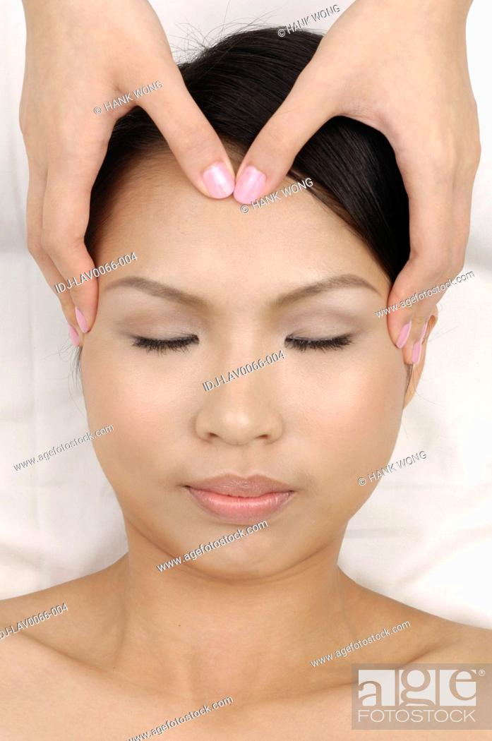 Stock Photo: Young woman getting face massage from a massage therapist.