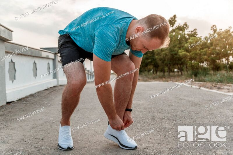 Stock Photo: portrait of Caucasian guy in a blue t-shirt and black shorts, who ties his laces on white sports shoes before Jogging.