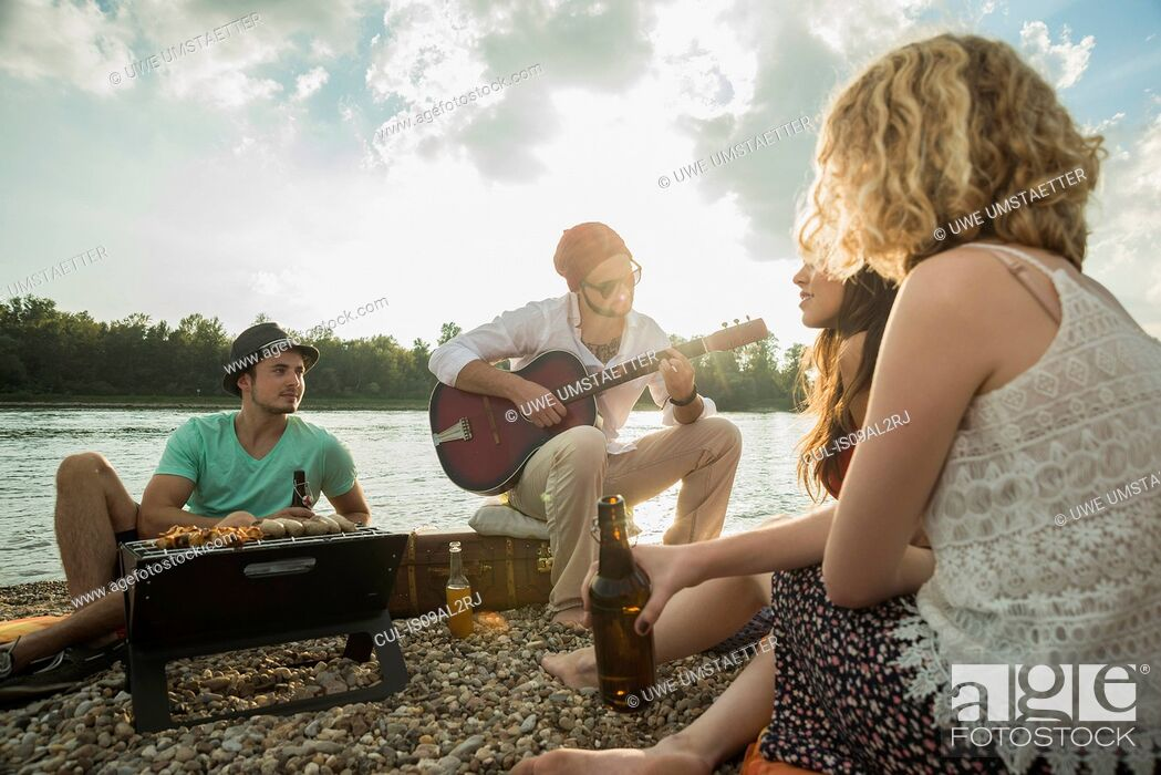 Stock Photo: Young man sitting by lake with friends playing guitar.