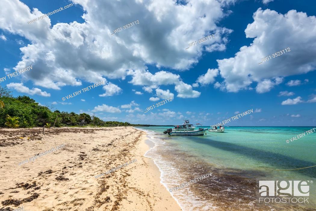 Stock Photo: Playa Palancar, Mexico - April 24, 2019: Boats on an empty Palancar beach in Playa Palancar, Quintana Roo, Mexico.