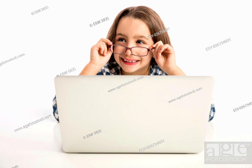 Stock Photo: Little girl sitting on a desk and working with a laptop.