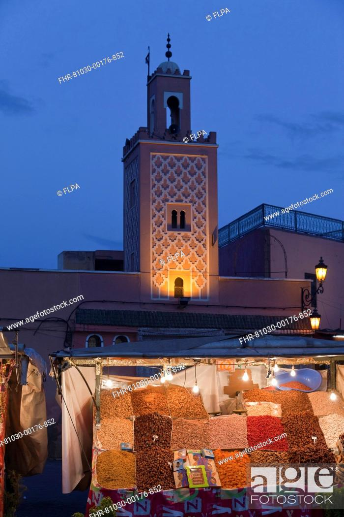 Stock Photo: Mosque minaret and market stand in city at dusk, Djemaa el Fna, Marrakesh, Morocco, april.