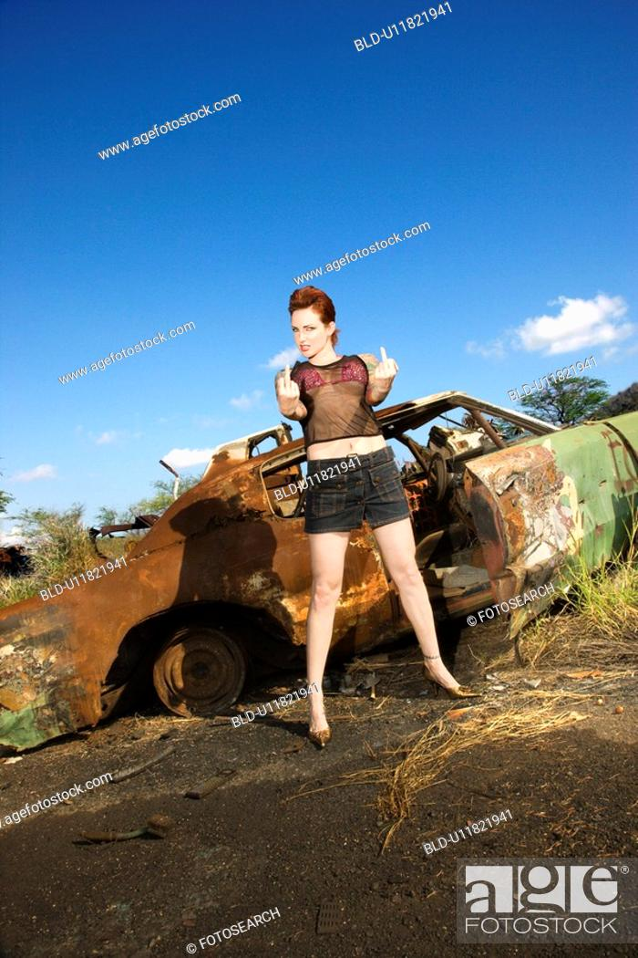 Stock Photo: Sexy tattooed woman standing giving middle finger in front of old rusted car in junkyard.