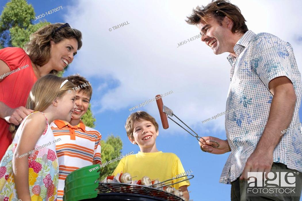 Stock Photo: Family with three children 6-11 grilling in garden.