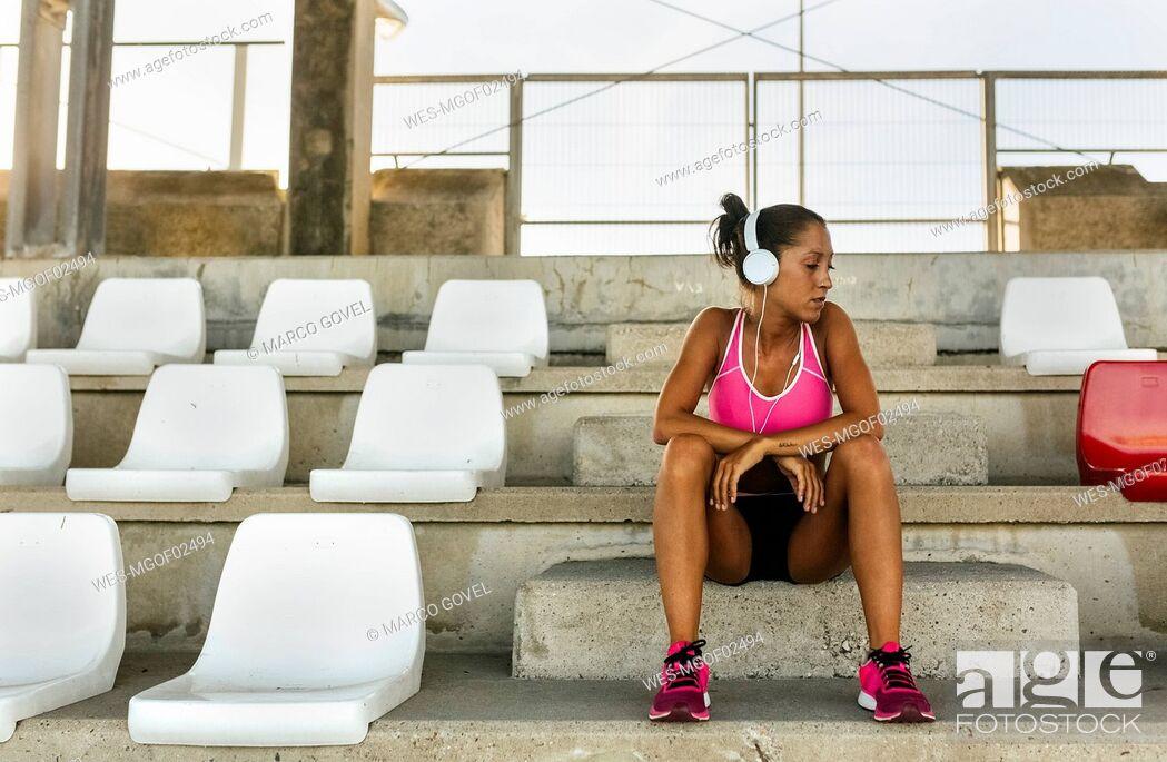 Stock Photo: Female athlete taking a break, listening to music.