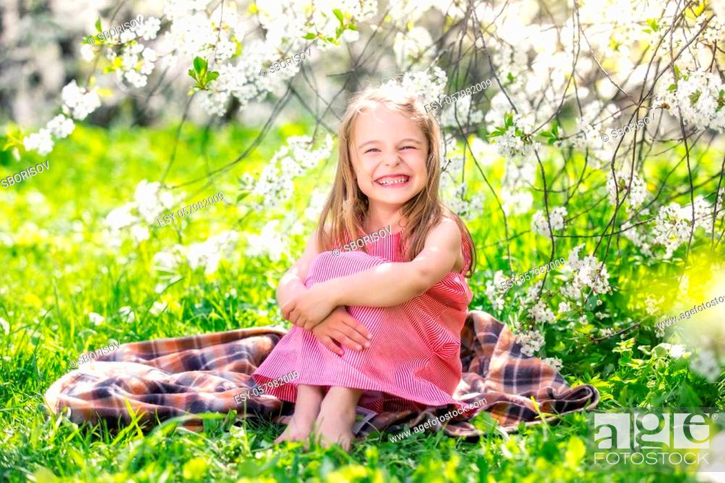Stock Photo: Happy little girl playing in spring cherry garden.