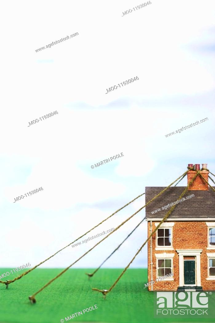 Stock Photo: Model house tied down with string.