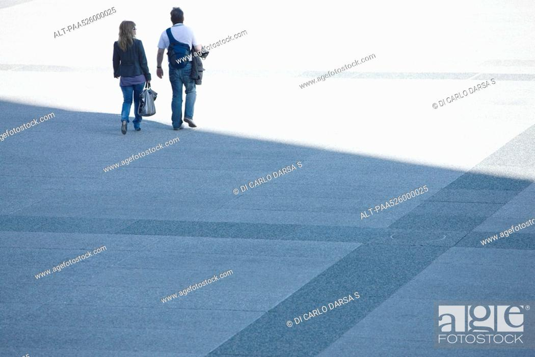 Stock Photo: Couple walking together across public square.