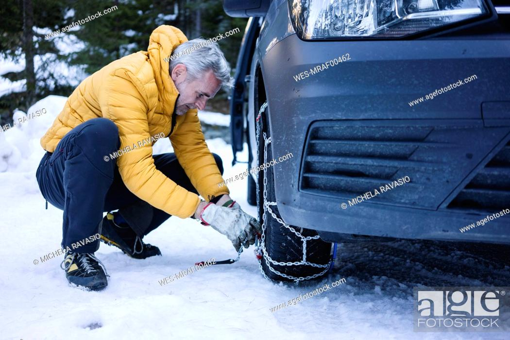 Stock Photo: Man putting the snow chains on his car.