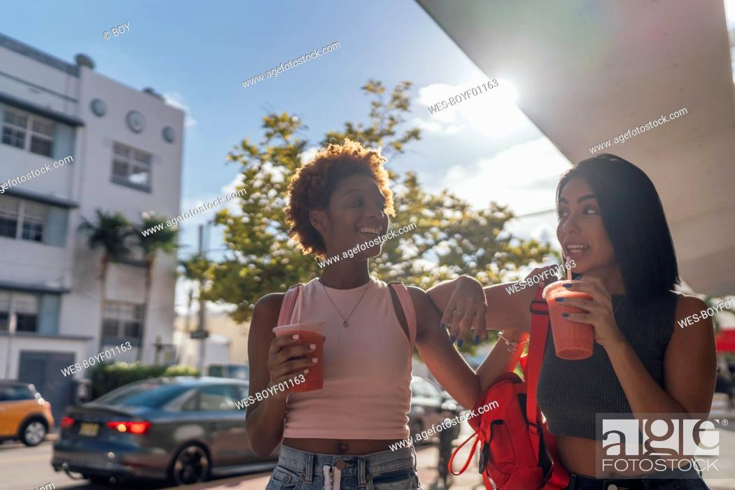 Stock Photo: USA, Florida, Miami Beach, two happy female friends having a soft drink in the city.