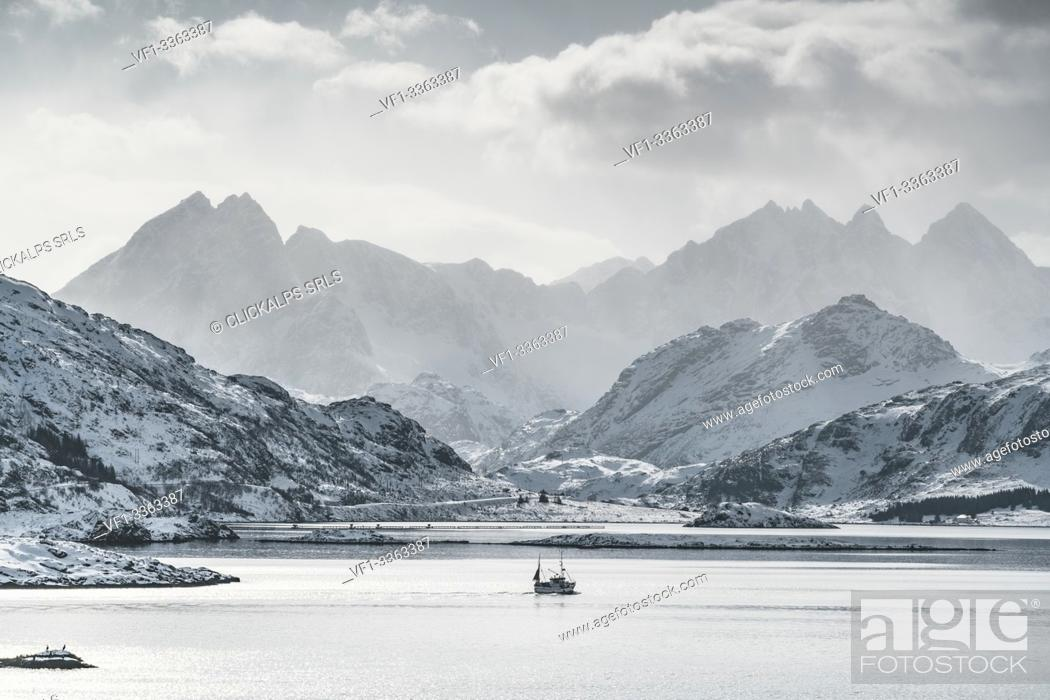 Stock Photo: Fishing boat sailing on the fjord, with Tekoppstetten peak in the background in winter. Fredvang, Flakstad municipality, Nordland county, Northern Norway.