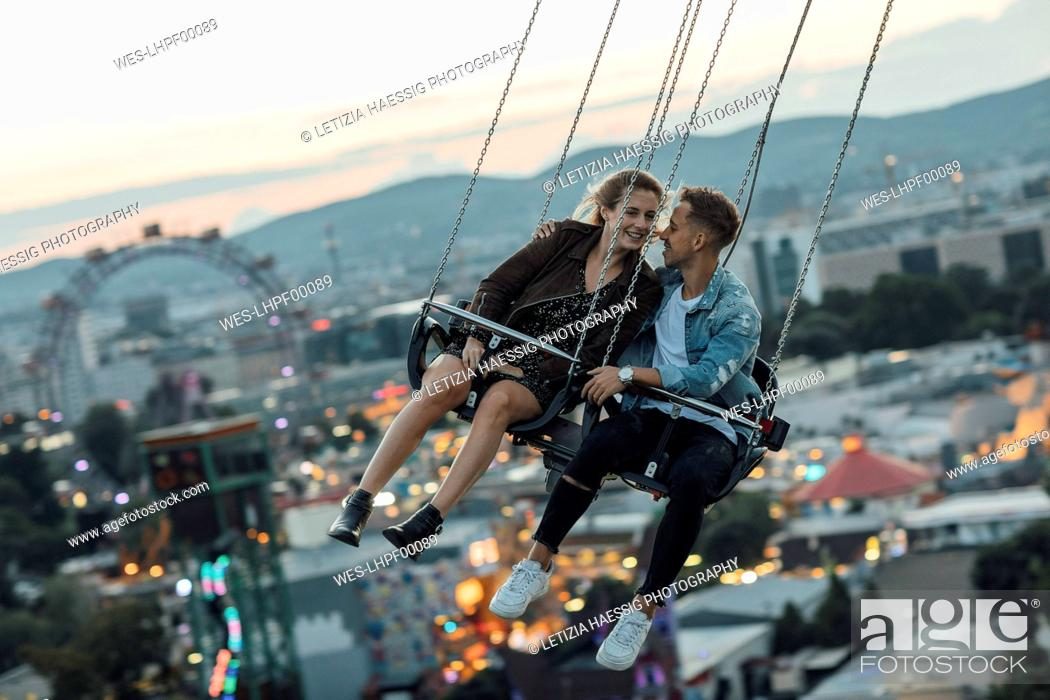 Stock Photo: Young couple in love, riding chairoplane on a fairground.